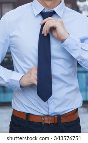 Close-up of Male office worker tying a tie