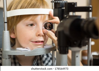 Closeup of male optician's hand checking boy's eye with lens in store