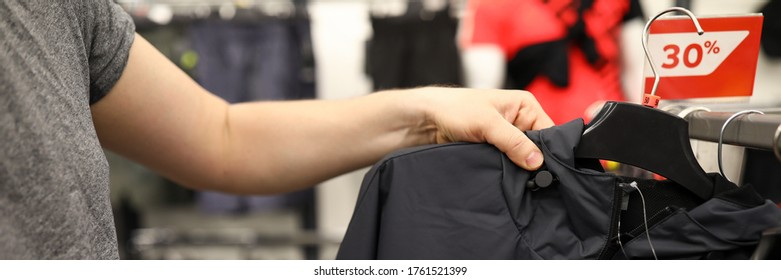 Close-up of male person choosing black casual jacket in shopping centre. Red discount on top clothes. Low price. Stylish purchase in mens department. Store concept