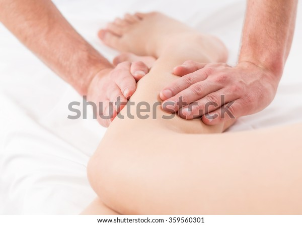 Close-up of male physiotherapist doing legs' massage
