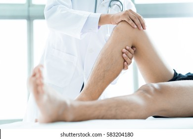 Close-up of male physiotherapist massaging the leg of patient in a physio room.
