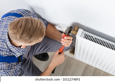 Close-up Of Male Plumber Fixing Thermostat Using Wrench At Home