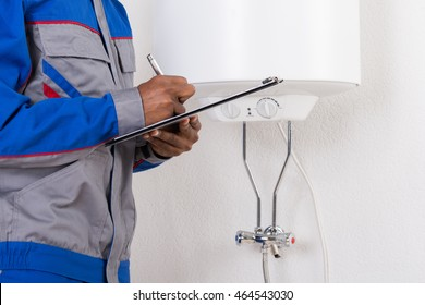 Close-up Of Male Plumber Writing On Clipboard