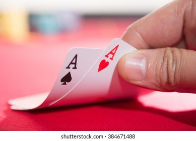 Close-up of male poker player lifting corners of two cards.