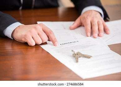 Close-up of male realtor is showing a contact with key from new apartment.