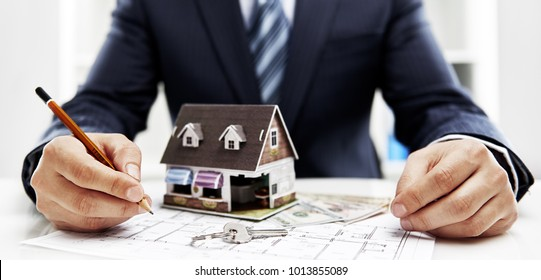 Closeup of male realtor sitting at the desk with house plan blueprint, key and house model.