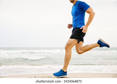 closeup male runner running sandy beach in background of sea and sky