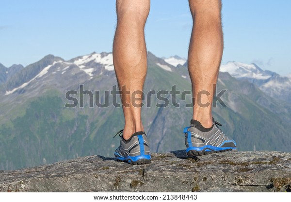 Closeup of male runner's bare legs in running shoes standing on top of rocky summit with magnificent scenic view of snow capped mountains in distance