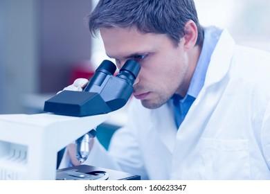 Close-up of a male scientific researcher using microscope in the laboratory