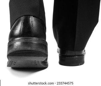 Closeup of male suit walking away in black worn shoes towards white