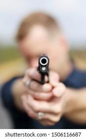 Closeup of a man aiming a pistol.
