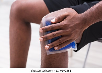 Close-up Of A Man Applying Ice Gel Pack On His Knee