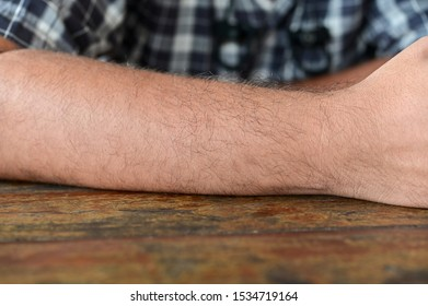 Closeup of man arm on wood table