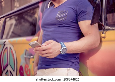 close-up of a man with athletic body holding a smartphone