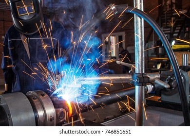 A close-up man is an auto mechanic in uniform in a welding mask welding metal on an automatic welding machine for repairing cardan shafts in an industrial workshop, sparks flying in the sides