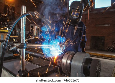 A close-up man is an auto mechanic in uniform in a welding mask cooking metal on an automatic welding machine for repairing cardan shafts in an industrial workshop, sparks flying in the sides