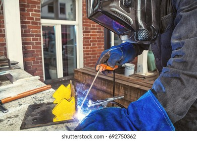 A close-up of a man in a black construction uniform, a welding mask, wired black gloves, welds a metal yellow construction on the table with a welding machine, a brick wall and a white old window