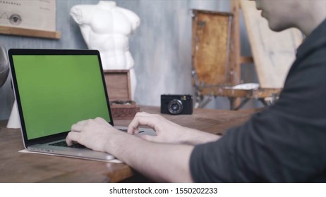 Close-up of man in black shirt sitting at the old table and typing on laptop with green chroma key screen. Stock footage. Laptop new technology concept, chroma key green screen