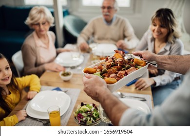 Close-up of man brining food at the table while having lunch with his family at home.