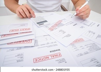 Close-up Of A Man Calculating Unpaid Bills Using Calculator