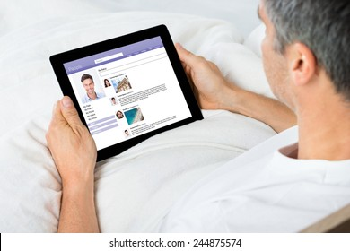 Close-up Of Man Chatting On Social Networking Sites Using Digital Tablet