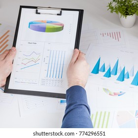 Closeup of a man checking accounts.  Stock market chart and finger pointing on tablet in office.