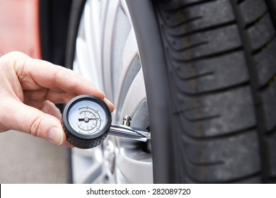 Close-Up Of Man Checking Car Tyre Pressure With Gauge