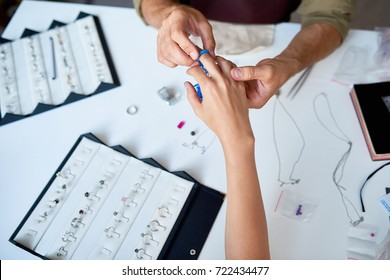 Closeup of man checking ring size of elegant female hand in jewelry shop
