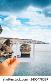 closeup of a man at the cliffs over the Mediterranean sea in Bonifacio, Corsica, in France, with a white frame in his hand framing the famous Grain de Sable sea stack, simulating an instant photograph