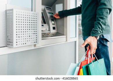 Closeup of man with colorful shopping bags withdrawing money from ATM machine