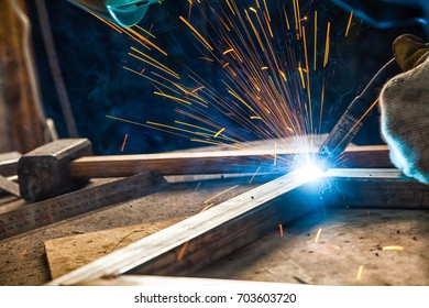 close-up man in construction gloves brews metal welding machine, a lot of blue sparks, a hammer on the table, a dark background