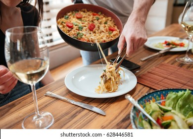 Closeup of man cooking dinner and putting food into the plate at the table