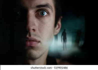 close-up of a man in a dark forest at night. Horror scene.