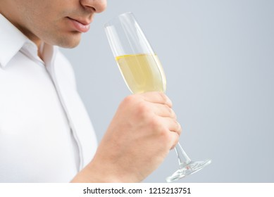 Closeup of man drinking champagne from goblet. Person holding goblet. Party concept. Isolated cropped view on grey background.