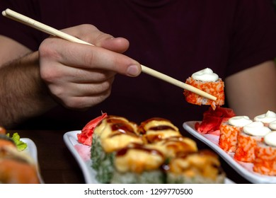 closeup man eating delicious sushi with two chopsticks with food in the background