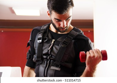 Closeup of man in EMS suit working on biceps
