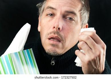 Close-up of a man exhausted by allergies/cold/flu holding a tissue and the box.