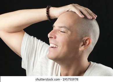 Close-up of a man feeling his newly shaved head.