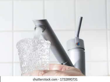 A closeup of a man filling up a glass with tap water