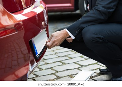 Close-up Of A Man Fixing New Empty White Number Plate On His Red Care