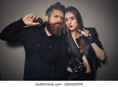 Close-up of man and girl smoking electronic cigarettes vape-mod and drip. Couple vaping. Vape addiction concept.Concept of smoking in public places is steam and smoke. There are clubs of steam.