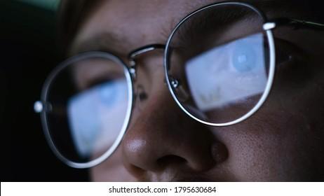 Gros plan sur un homme avec des lunettes regardant un ordinateur la nuit. Concept. Travailler à l'ordinateur dans le noir est mauvais pour la vue. Un homme avec des lunettes regarde attentivement l'ordinateur dans le noir