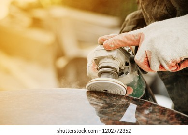 close-up a man in gloves polishes a marble monument with an angle grinder on a blurred background. grinding stone.
