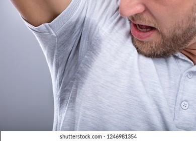 Close-up Of A Man In Grey T-shirt Looking At His Sweaty Armpit