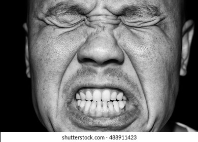 Closeup of a man grimacing. Processed in monochrome.