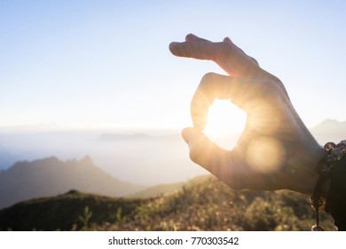 Close-up of man hand catch the beautiful moment of the morning sun on top of mountain, watching the sunrise.