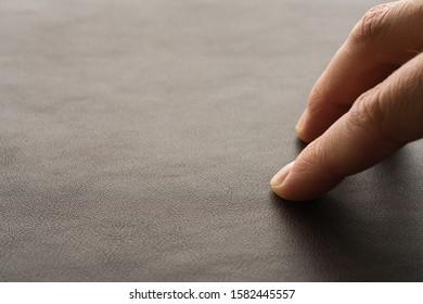 Closeup man hand check dark brown full grain leather
