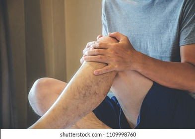 Closeup man hand holding knee with pain on bed, health care and medical concept