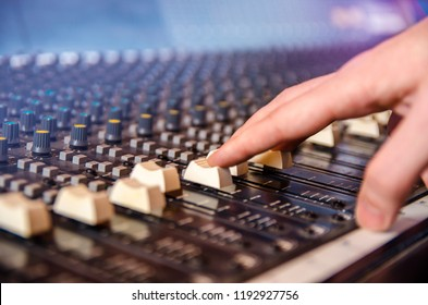 Closeup man hand on analog mixing table / console
