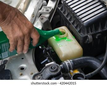 closeup of a man hand refill coolant into radiator engine